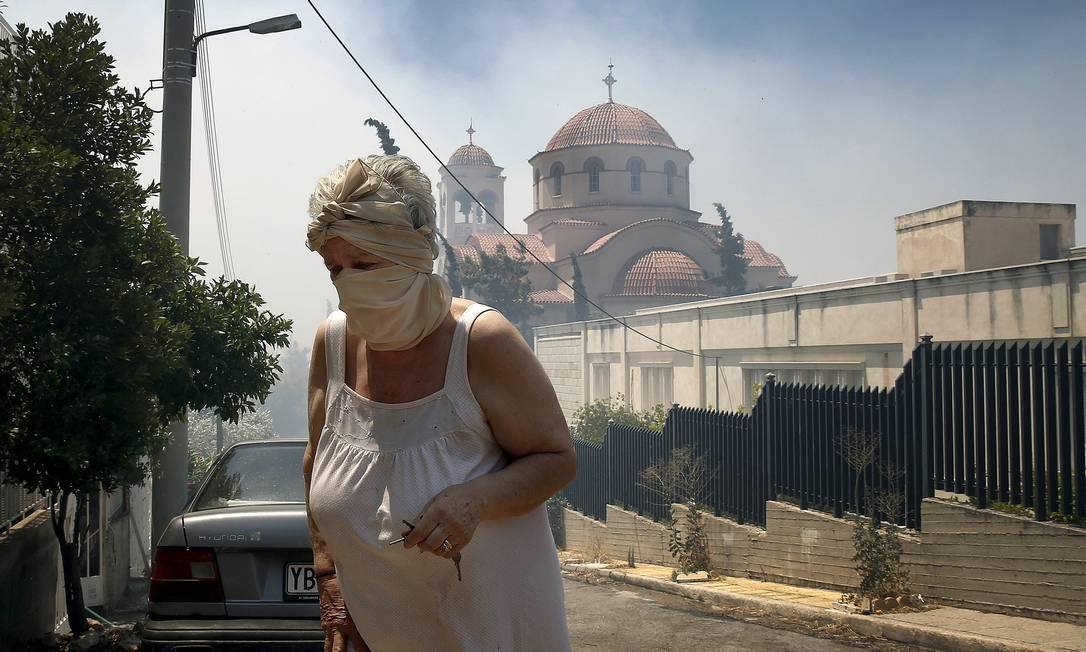 Mulher cobre o rosto com lenço para se proteger da fumaça YANNIS BEHRAKIS / REUTERS