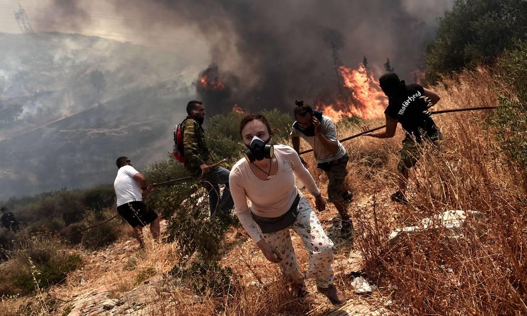 Pessoas usam máscaras para se proteger da fumaça, enquanto fogem das chamas ARIS MESSINIS / AFP