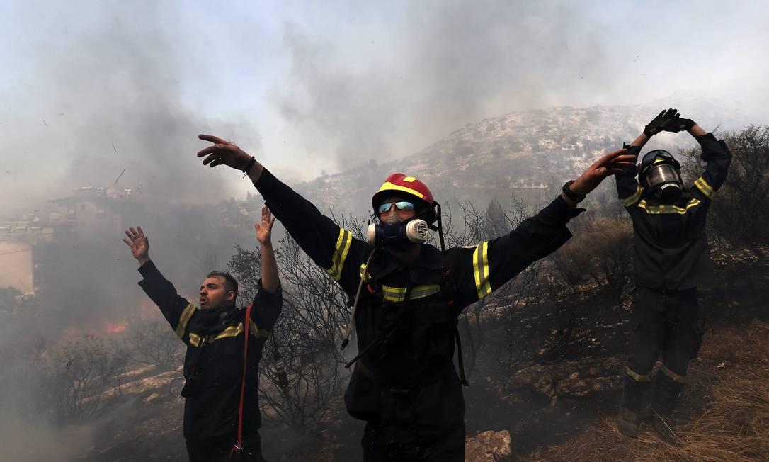 Bombeiros orientam helicópteros durante os trabalhos no Monte Yemette Giannis Liakos / AP