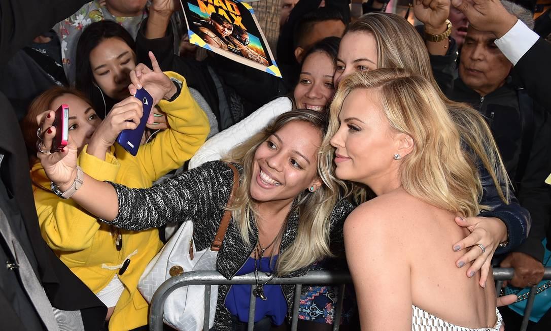 Charlize Theron: fotos com fãs no tapete vermelho KEVIN WINTER / AFP