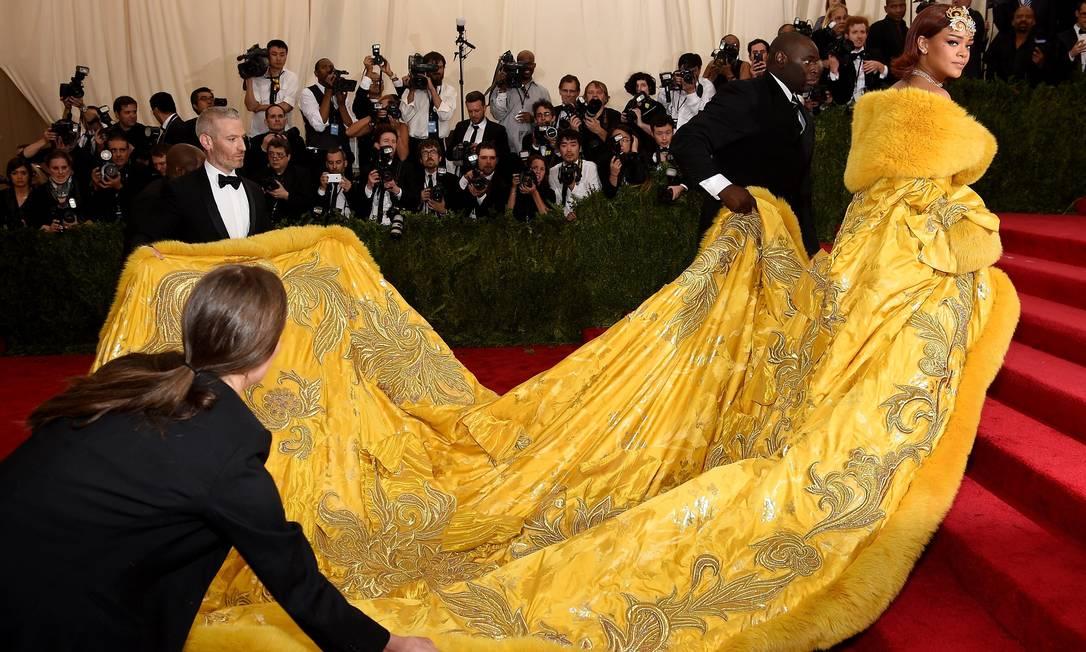 Rihanna e seus assistentes de red carpet Dimitrios Kambouris / AFP