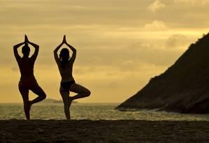 Mulheres praticam ioga na praia de Itacoatiara, em Niterói Foto: Guilherme Leporace / Agência O Globo