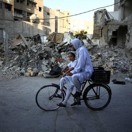 Homem sírio pedala com criança por destroços de um prédio em Damasco Foto: ABD DOUMANY / AFP