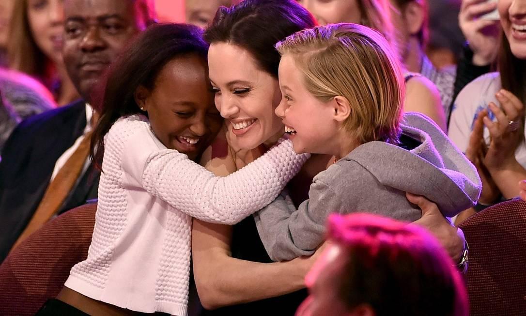 Nada melhor que o carinho das filhas antes de subir de receber um prêmio. Que o diga Angelina Jolie, a grande estrela do Kids' Choice Awards, que aconteceu no sábado, na Califórnia. Premiada como a melhor vilã por seu papel em Malévola, ela fez a festa com Zahara, à esquerda, e Shiloh, à direita KEVIN WINTER / AFP