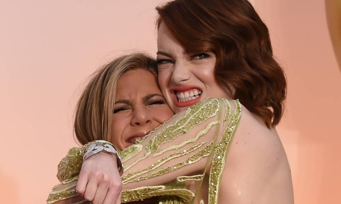Emma Stone foi uma das estrelas que mais se divertiu no evento. Aqui, ela dá um superabraço em Jennifer Aniston MARK RALSTON / AFP