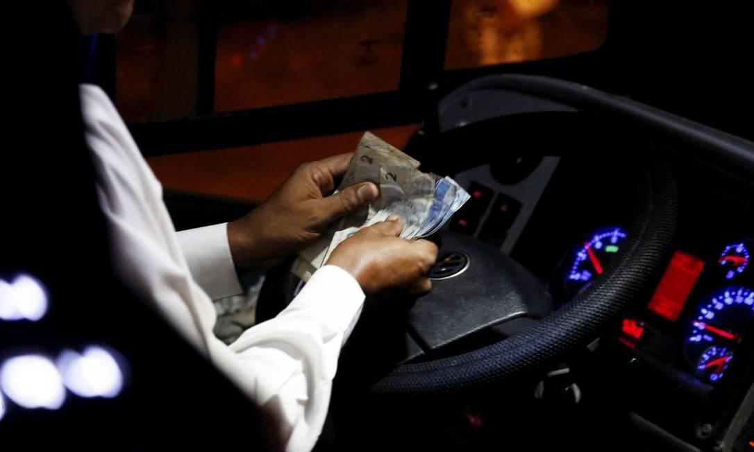 Com o dinheiro e o volante nas mãos, motorista faz a dupla função e anuncia o fim da profissão de cobrador Foto: Custódio Coimbra / Agência O Globo
