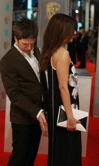 O músico Noel Gallagher, que fez parte da banda Oasis, fez gracinha com a mulher Sara, no red carpet do BAFTA. Mas o que era só ameaça se concretizou nos instantes seguintes... JUSTIN TALLIS / AFP