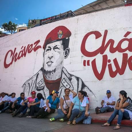 Venezuelanos se sentam em frente a muro pintado com a imagem de Hugo Chávez Foto: FEDERICO PARRA / AFP