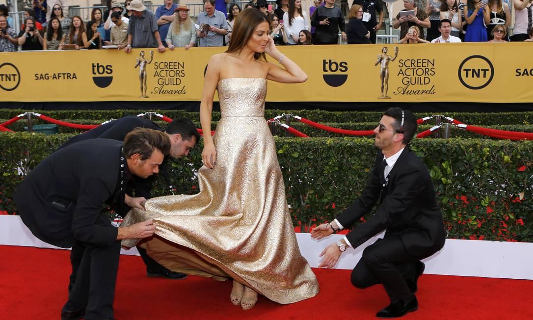 A apresentadora do E! Maria Menounos precisou de três pessoas para ajustar seu vestido MIKE BLAKE / REUTERS