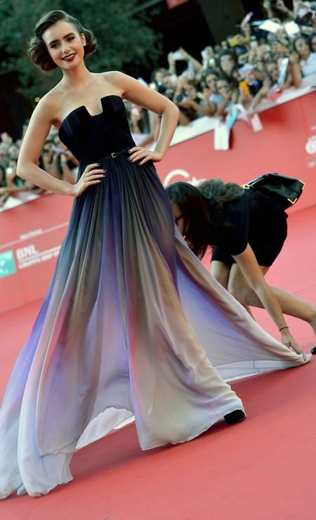 """O Festival Internacional de Cinema de Roma segue animado. A atriz Lily Collins, que está na capital italiana para divulgar o filme """"Love, Rosie"""", precisou de uma ajuda para ficar bem na foto. Uma assistente ajustou seu vestido em pleno tapete vermelho TIZIANA FABI / AFP"""