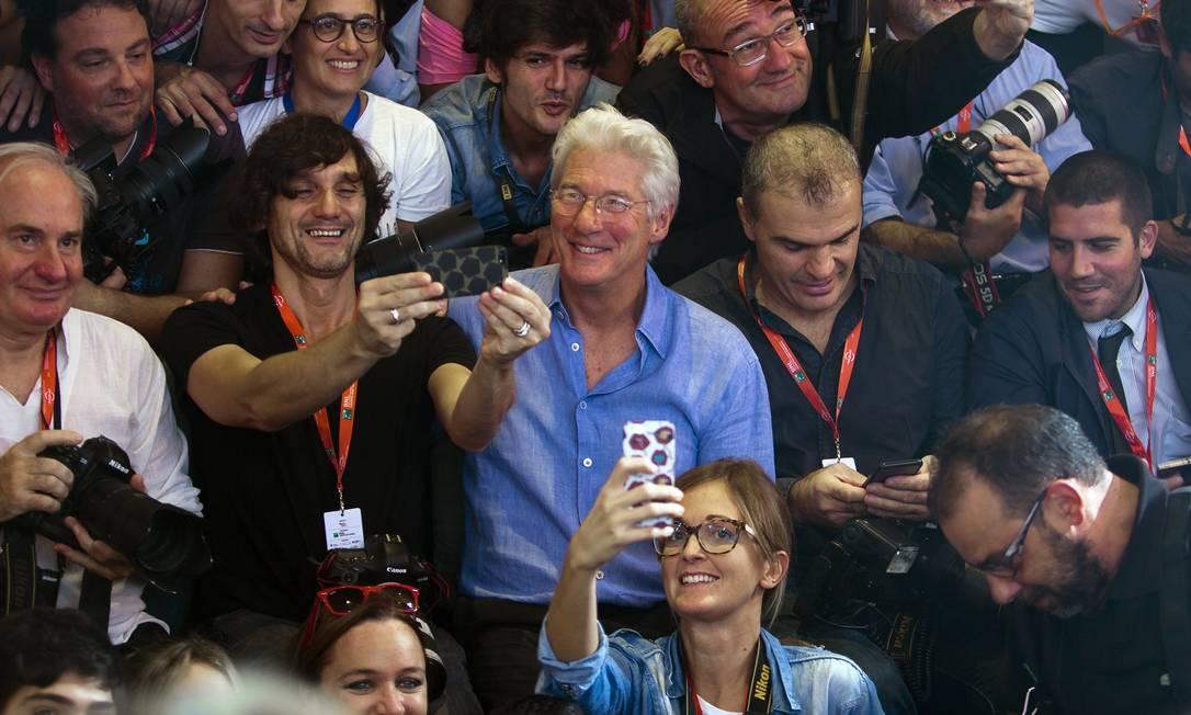 Enquanto Benicio del Toro fazia graça para as câmeras, Richard Gere fez um selfie com os fotógrafos Domenico Stinellis / AP