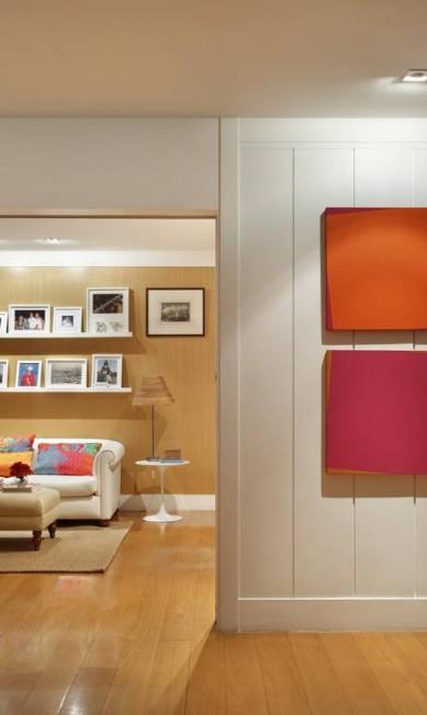 Nas prateleiras muitas fotos e mesinha lateral Saarinen. Os quadros coloridos são de Chico Fortunato divulgação / MCA Studio