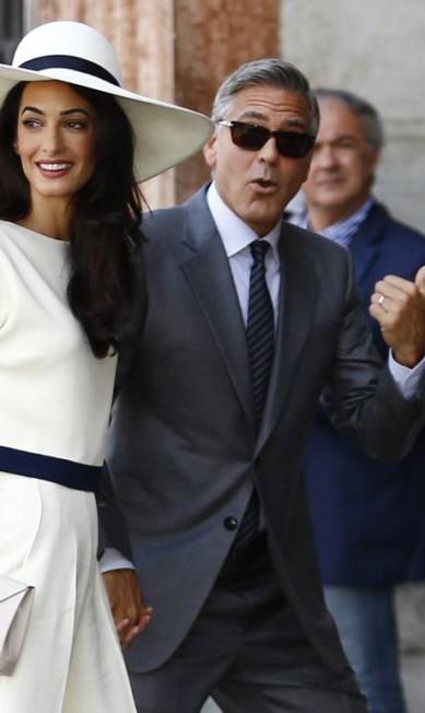 Para o casamento civil, Amal escolheu um macacão branco com detalhe azul-marinho PIERRE TEYSSOT / AFP