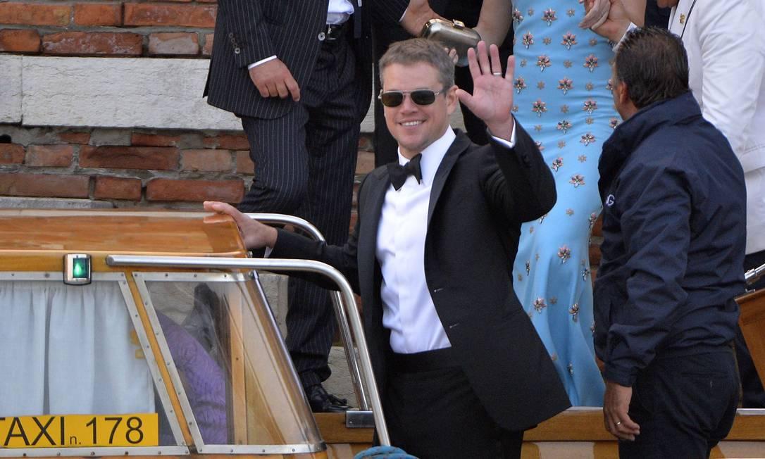 O ator Matt Damon acena enquanto embarca numa balsa em ao deixar o casamento de Clooney ANDREAS SOLARO / AFP