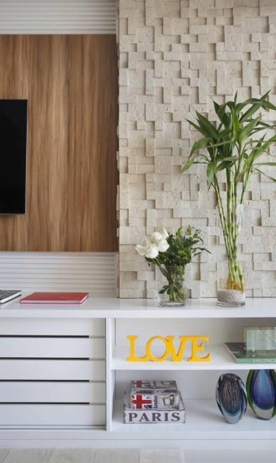 Marcenaria pintada de branco compõe um dos lados do living. que também foi revestido com um painel de pedras irregulares MCA Studio / Divulgação