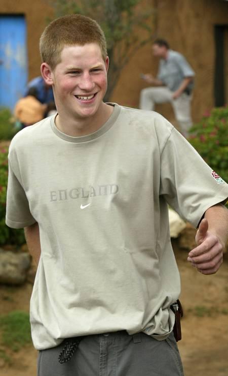 De cabeça raspada, em hospital no Lesoto, em 2004. O príncipe assumiu o trabalho que sua mãe, Diana, fez em prol dos portadores do HIV Foto: Ben Curtis / AP Photo