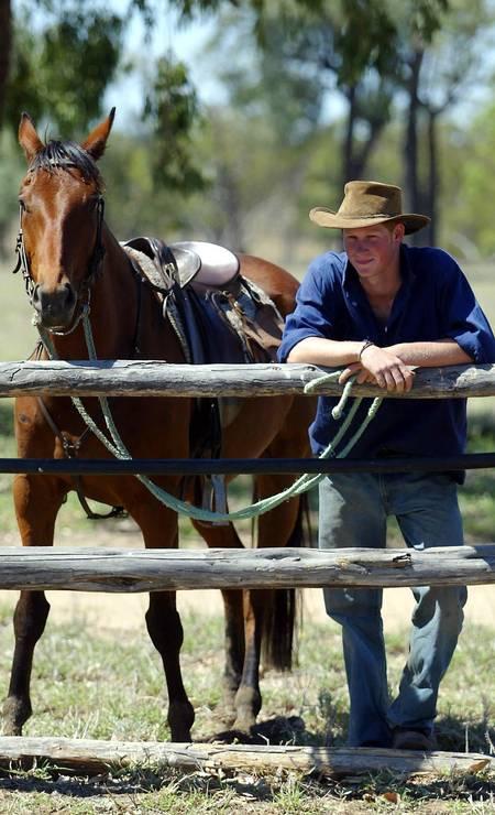 Com pose de vaqueiro: Harry ao lado do seu cavalo, Guardsman, em rancho em Tooloombilla, na Austrália, em 2003 Foto: Gareth Copley / AP Photo/PA, Gareth Copley
