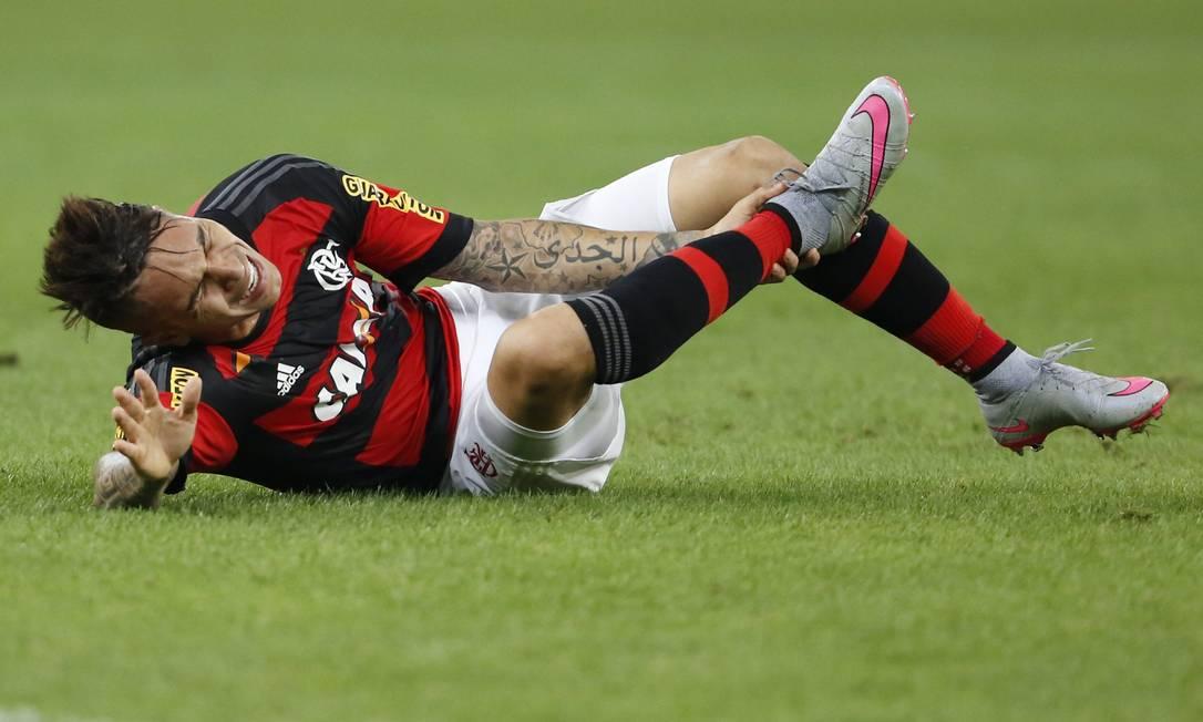 Guerrero faz cara de dor e põe a mão no tornozelo direito, atingido com violência por um jogador do Grêmio Guito Moreto / Agência O Globo