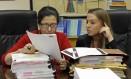 As advogadas Grisel Ybarra e Monica Barba Neumann olham documentos em escritório, em Miami. Elas representam clientes que podem enfrentar a deportação Foto: Alan Diaz / AP / 16/07/2015