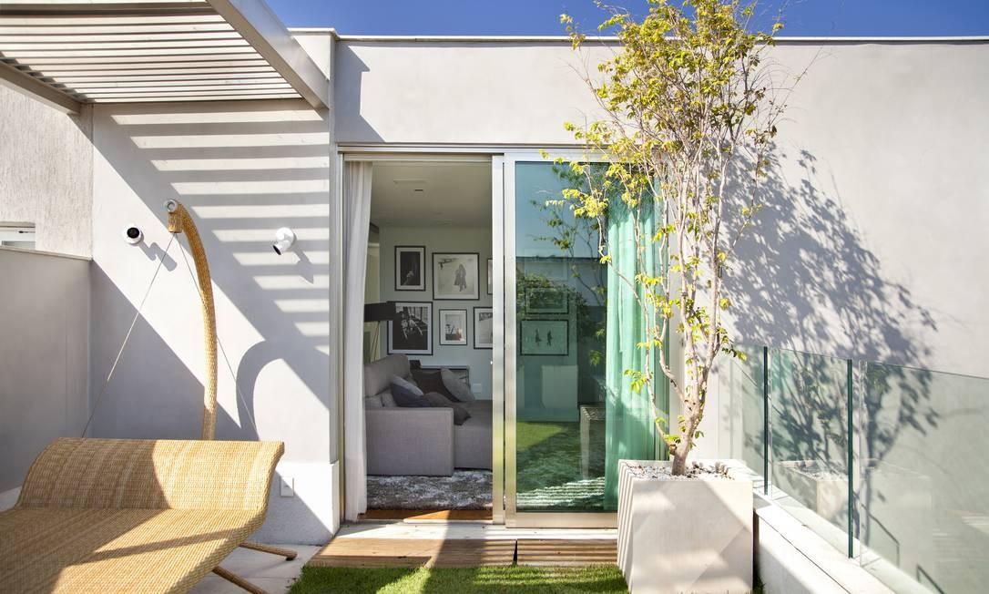 Minimalismo nos móveis da varanda. A grama dá uma cara de casa ao apartamento Foto: MCA Studio