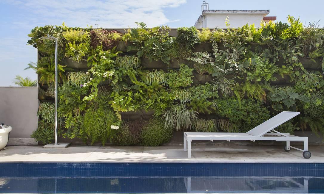 Ladeando a piscina em forma de raia, o jardim vertical traz o verde para a varanda MCA Studio