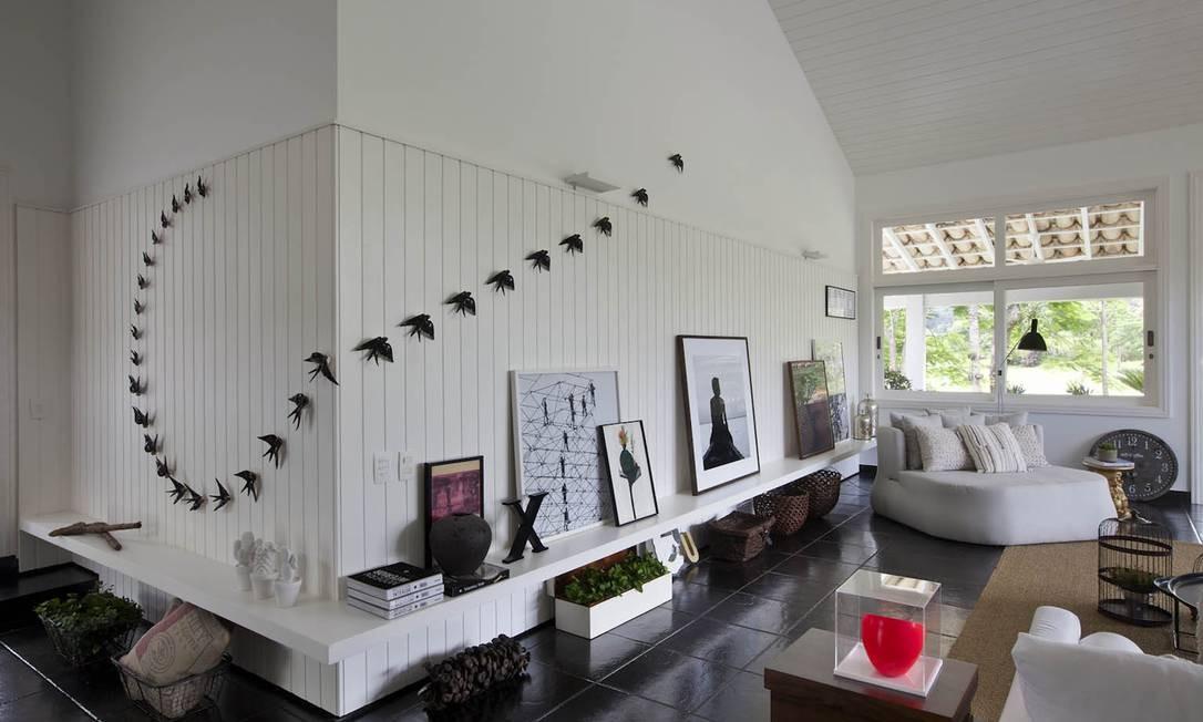 Na entrada do living, as boas-vindas com a instalação da revoada de pássaros feita por Gabriela Albergaria Foto: Photographer: Demian Golovaty / Divulgação