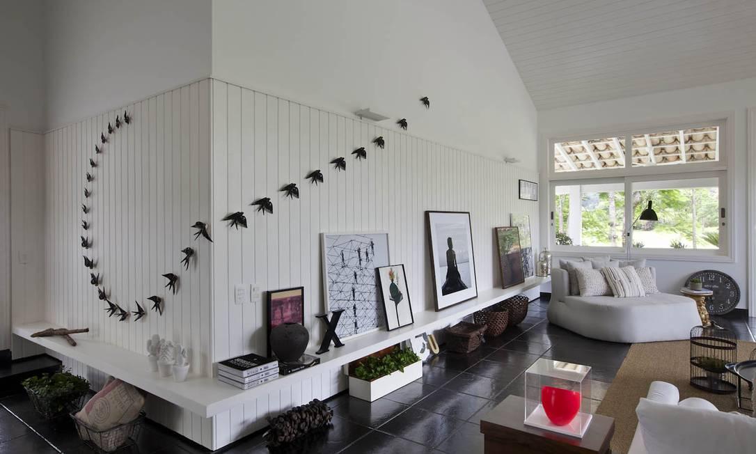 Na entrada do living, as boas-vindas com a instalação da revoada de pássaros feita por Gabriela Albergaria Photographer: Demian Golovaty / Divulgação