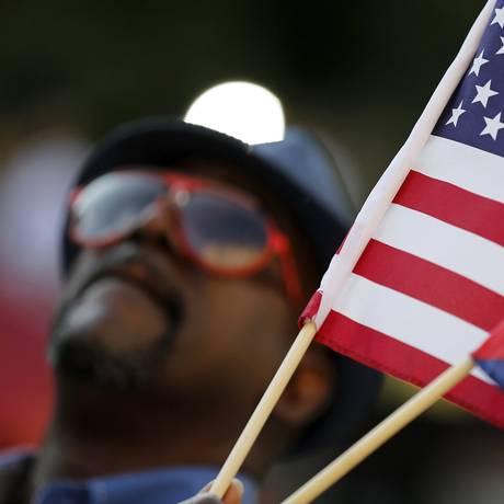 Homem com bandeiras de Cuba e dos Estados Unidos horas antes de funcionários hastearem bandeira na sede da Embaixada de Cuba, em Washington. Os dois países inauguraram uma nova era de relações pós-Guerra Fria, restaurando relações diplomáticas cortadas há mais de cinco décadas Foto: 20/07/2015 / Jonathan Ernst / Reuters