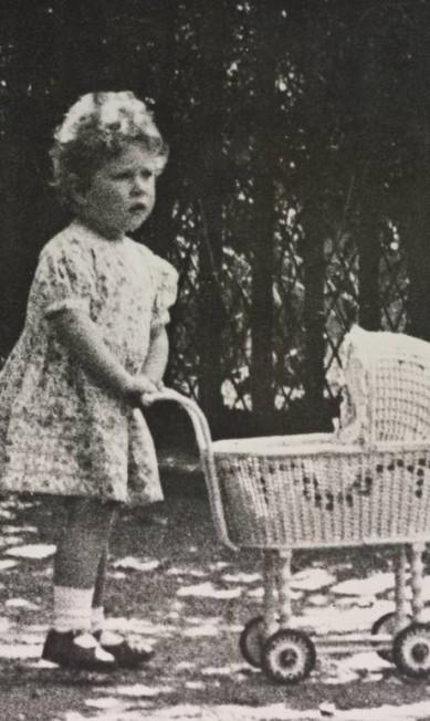 A então princesa Elizabeth aos dois anos, com seu carrinho de bebê de brinquedo Royal Collection Trust / (C) Her Majesty Queen Elizabeth II 2014.