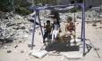 Crianças palestina brincam em balanço perto de destroços de prédios atingidos na guerra do ano passado entre Israel e Hamas