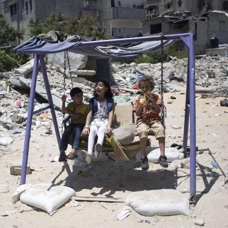 Crianças palestina brincam em balanço perto de destroços de prédios atingidos na guerra do ano passado entre Israel e Hamas Foto: SAID KHATIB / AFP