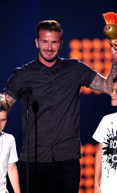 Antes do banho de tinta, o inglês subiu ao palco com os filhos Cruz (à esquerda), de 9 anos, e Romeo (à direita), de 12, para receber o prêmio KEVIN WINTER / AFP