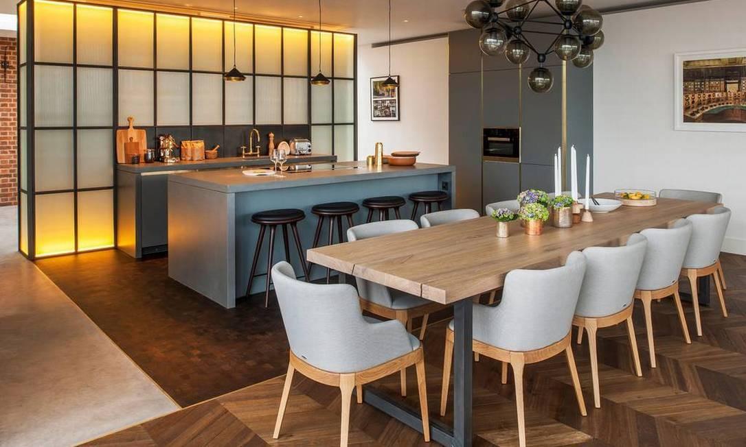 Cozinha integrada com sala de jantar: ilha de concreto faz referência ao passado industrial Divulgação