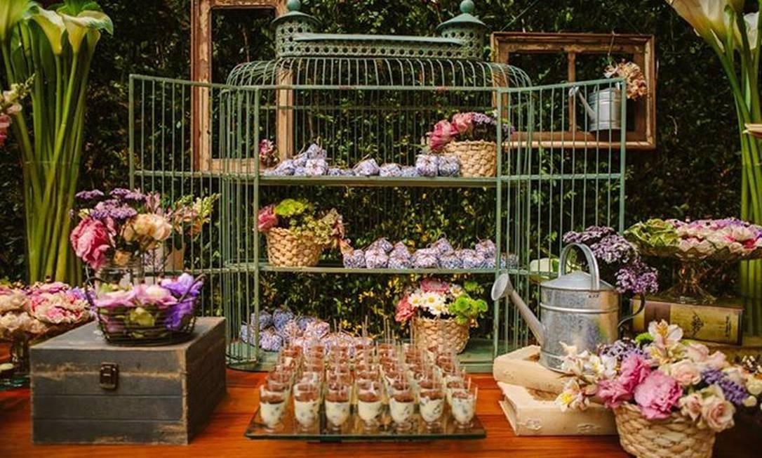 Mesa de casamento decorada com gaiola, regadores, flores e cestos Foto: Divulgação / Divulgação