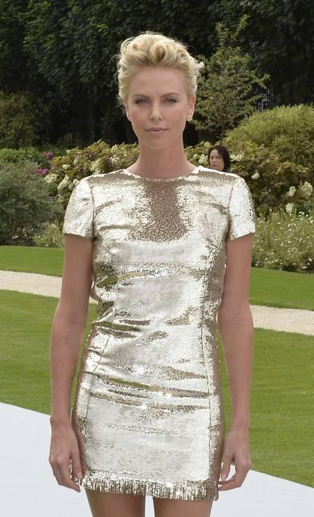 Charlize foi a grande estrela da primeira fila do desfile da Dior. Ela usou um vestidinho metalizado da maison Foto: MIGUEL MEDINA / AFP