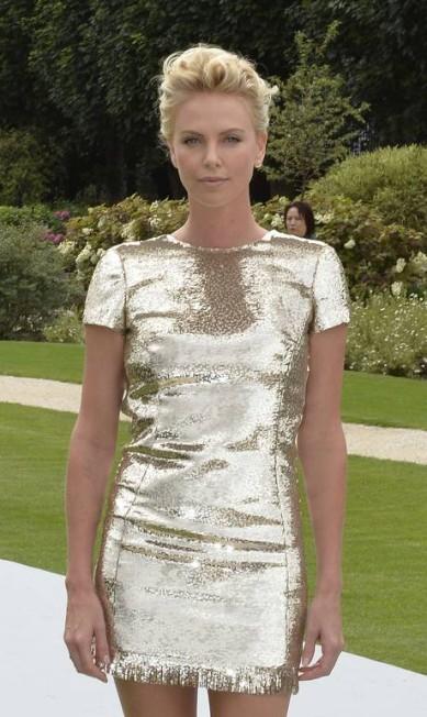 Charlize foi a grande estrela da primeira fila do desfile da Dior. Ela usou um vestidinho metalizado da maison MIGUEL MEDINA / AFP