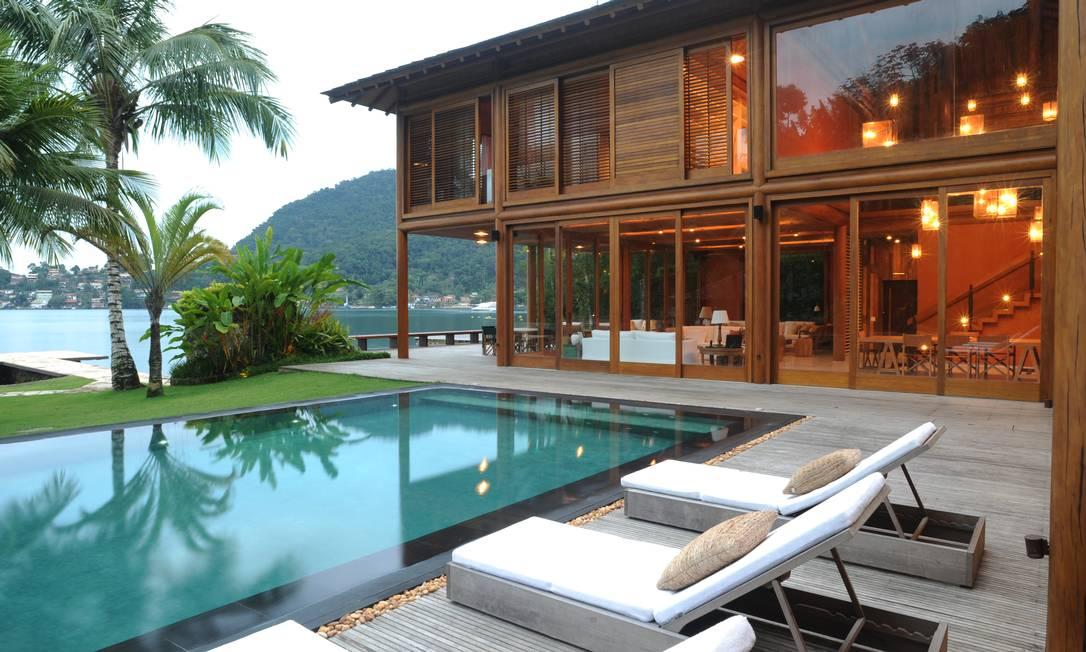 A casa principal se abre para a piscina de pedras javanesas com borda de pedras vulcânicas e para a paradisíaca vista do mar de Angra Joaquim Nabuco