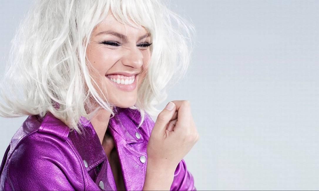 Em outro momento da campanha, Candice aparece de peruca platinada e sorridente Divulgação