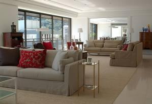 O living do apartamento tem dois ambientes, com predomínio do tom bege quebrado pelas almofadas vermelhas sobre sofás revestido de linho Foto: Divulgação
