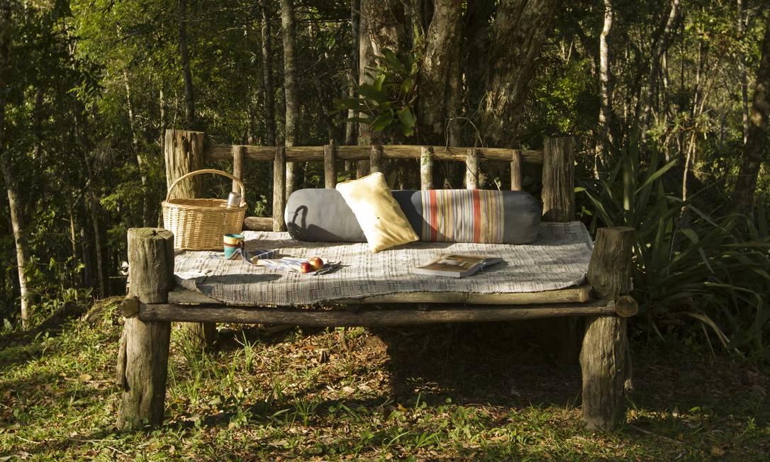 No gramado ao redor da casa, cantinhos acolhedores com bancões de madeira e almofadas Secre 1 / Divulgação