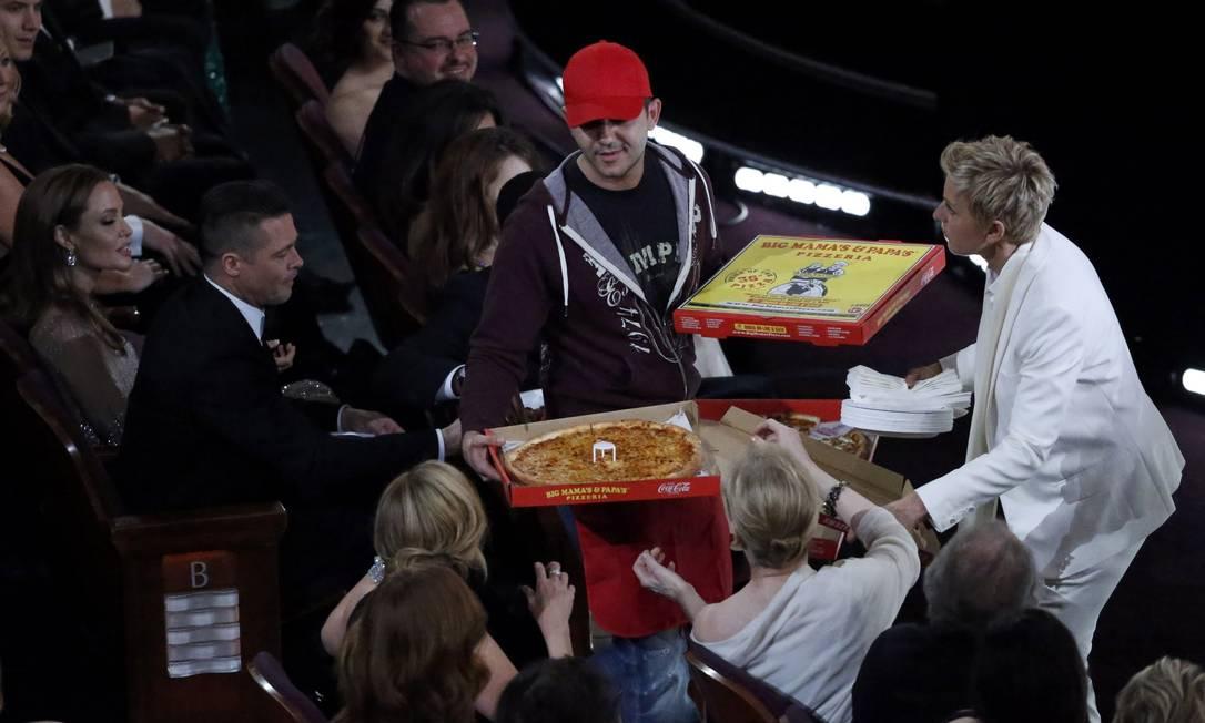 A apresentadora Ellen DeGeneres distribui pizza para os convidados. Entre eles, Brad Pitt e Angelina Jolie LUCY NICHOLSON / REUTERS
