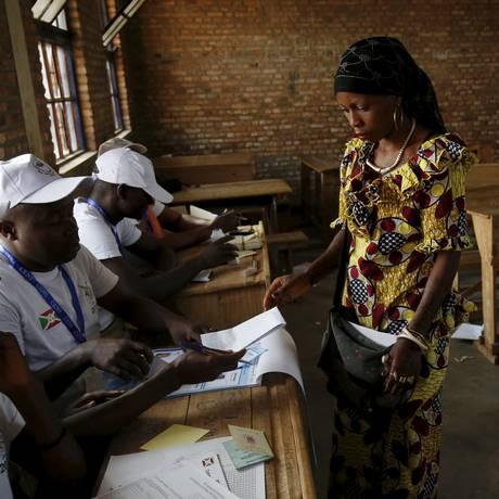 Mulher recebe cédulas em seção eleitoral na capital Bujumbura Foto: Mike Hutchings / Reuters