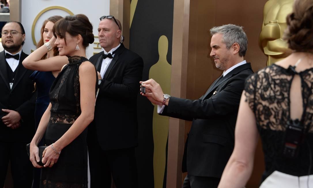 """Indicado ao Oscar de Melhor Diretor, por """"Gravidade"""", Alfonso Cuarón fez questão de registrar até as costas do vestido de Sheherazade Goldsmith ROBYN BECK / AFP"""