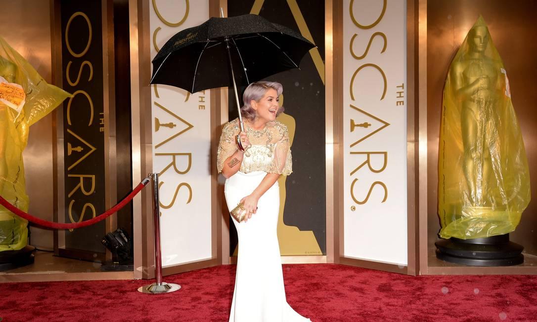 Kelly Osbourne bem que tentou manter a pose, mas de guarda-chuva ficou difícil Jason Merritt / AFP
