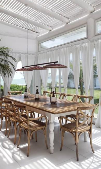 A mesma mesa por outro ângulo: vidros deixam vista para o mar evidente Divulgação