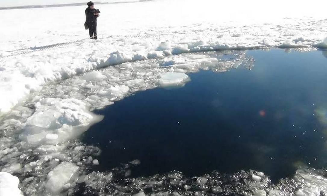 5) A tradição na Sibéria requer coragem e dose extra de força: mergulhar em um lago congelado e, ainda, carregando uma árvore Foto: AP