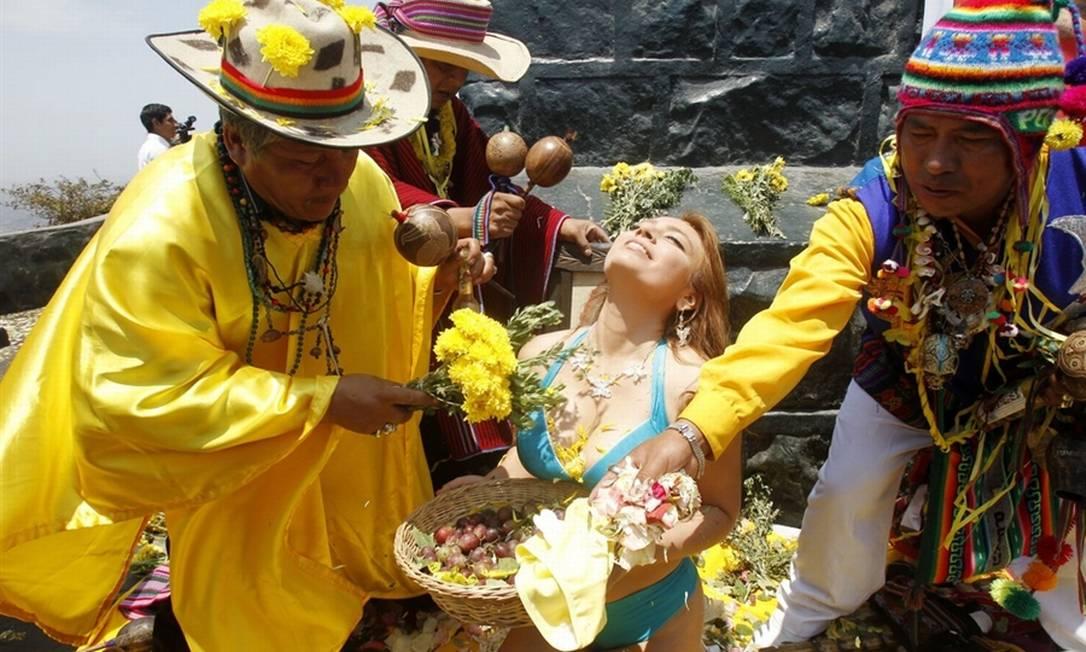 7) No Peru, é costume ocorrer uma briga entre os vizinhos para resolver disputas antigas. Na foto, outro ritual do país: uma mulher segura uma oferenda de frutas para trazer boa sorte para o novo ano Reuters