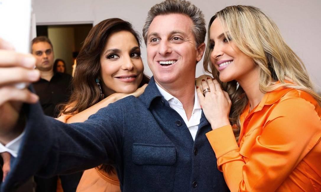 No início de outubro, as duas divas tiveram em São Paulo para o lançamento do produto e posaram junto com o amigo e apresentador Luciano Huck, que nesta imagem faz um registro do encontro Divulgação