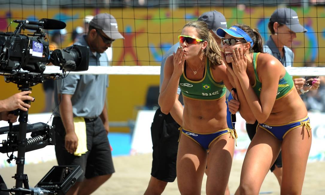 As brasileiras Liliane Maestrini (esquerda) e Carolina Horta fazem graça para a câmera de TV depois de conquistar a medalha de bronze, em jogo contra o Canadá HECTOR RETAMAL / AFP