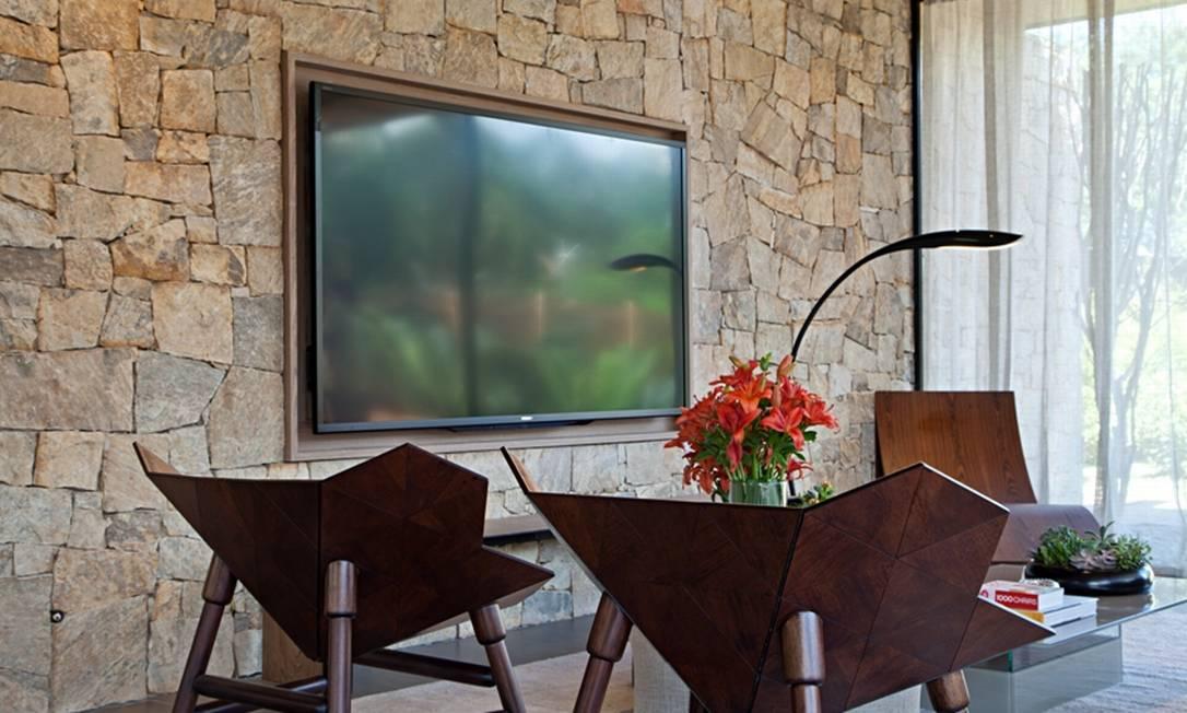 Na casa de fim de semana de Duda Porto, a TV ganha uma espécie de moldura de madeira sobre a parede de pedra Divulgação/Rodrigo Azevedo